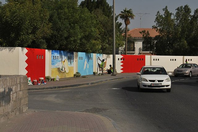 Near the 'Bulls head' roundabout in Sehla, Bahrain, a 'beautification' team paint walls with images of pearl divers, dhows and oysters.  Photograph by Amal Khalaf.