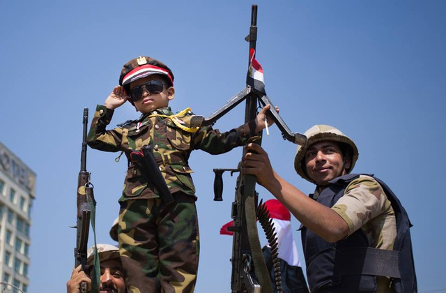 Child dressed in military fatigue imitating Sisi.