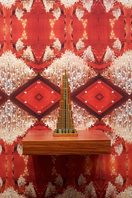 "<p style=""text-align: justify;"">Pio Abad, <em>Oh! Oh! Oh! (A Universal History of Iniquity)</em>, Digitally printed wallpaper depicting a chandelier designed by Leandro Locsin for the Philippine International Convention Centre, plastic perfume bottles purchased from Whitechapel Market in the shape of a camel, a palace, a scimitar, the Burj al Arab and the Burj Khalifa, and narra wooden shelves. Dimension variable. 2013. Copyright and courtesy the artist.</p>"