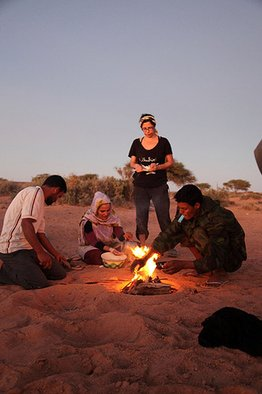 <p>Robin Kahn's 2009 project at ARTifariti</p><p>Kahn (standing) & Nigela with Cousins Baking Bread in the Sand, outside Tifariti</p><p>The Liberated Territories of Western Sahara</p><p>Image courtesy of the artist</p>