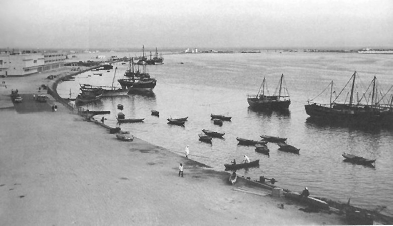 The Deira side of Dubai Creek in 1964, after reclaimed land had been added to the shore. Dhows were offloaded by smaller vessels. Port Saeed would be developed further upshore in photograph's background.