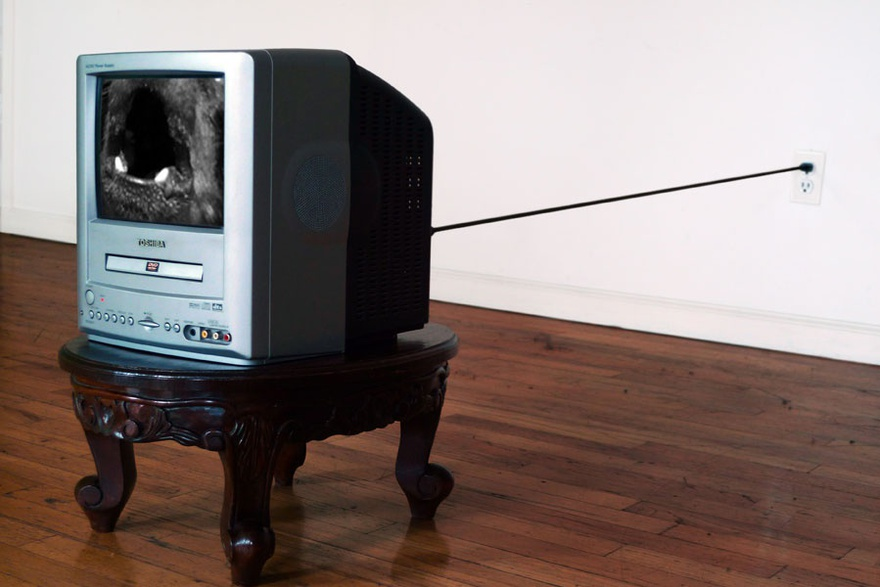 Nida Sinnokrot, Barking Dog, 2000. T.V, carved wood stool, DVD, dimensions variable.