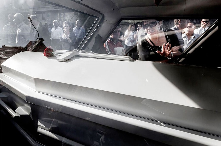 Carole Alfarah. People surround the hearse transporting the coffin of 19-year-old Maria Kahla, who was killed with her father and her two friends in a suicide car bombing as they were heading to university early morning in a Damascus neighborhood. Damascus, Syria, 2012.