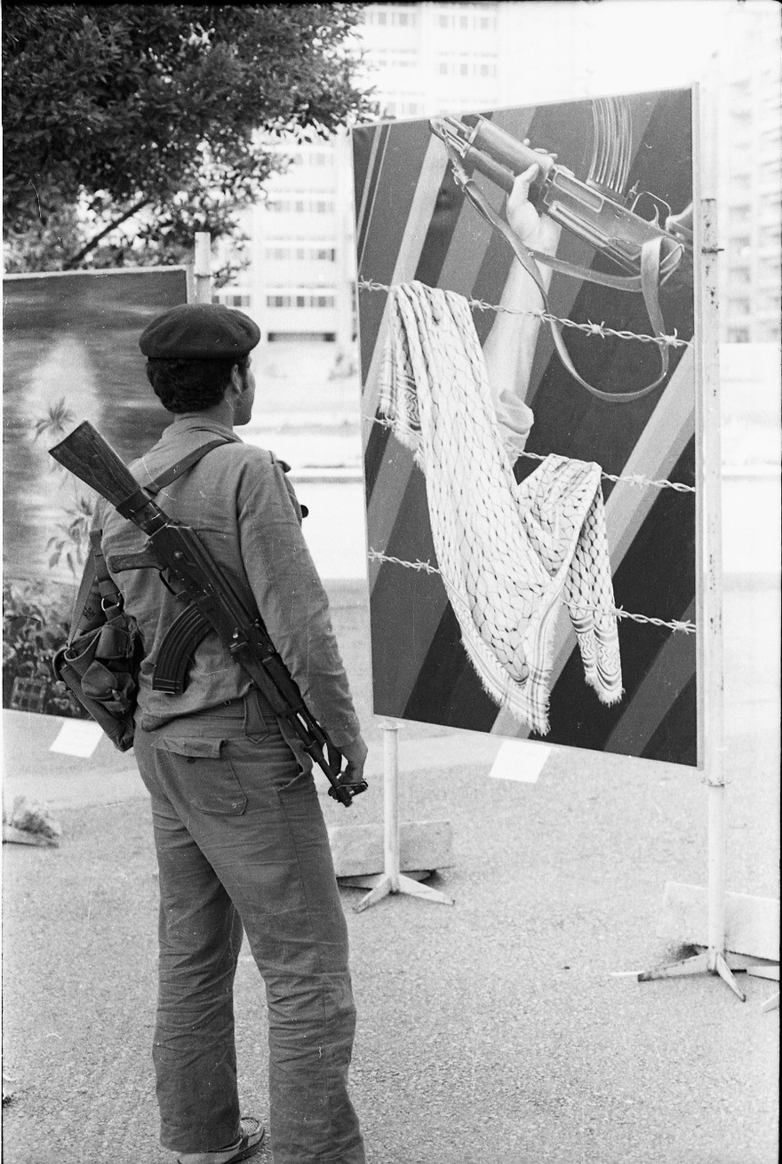 Palestinian fighter looking at artwork by Claude Lazar at 15 May Exhibition, Day of the Palestinian Struggle, Beirut, 1978.