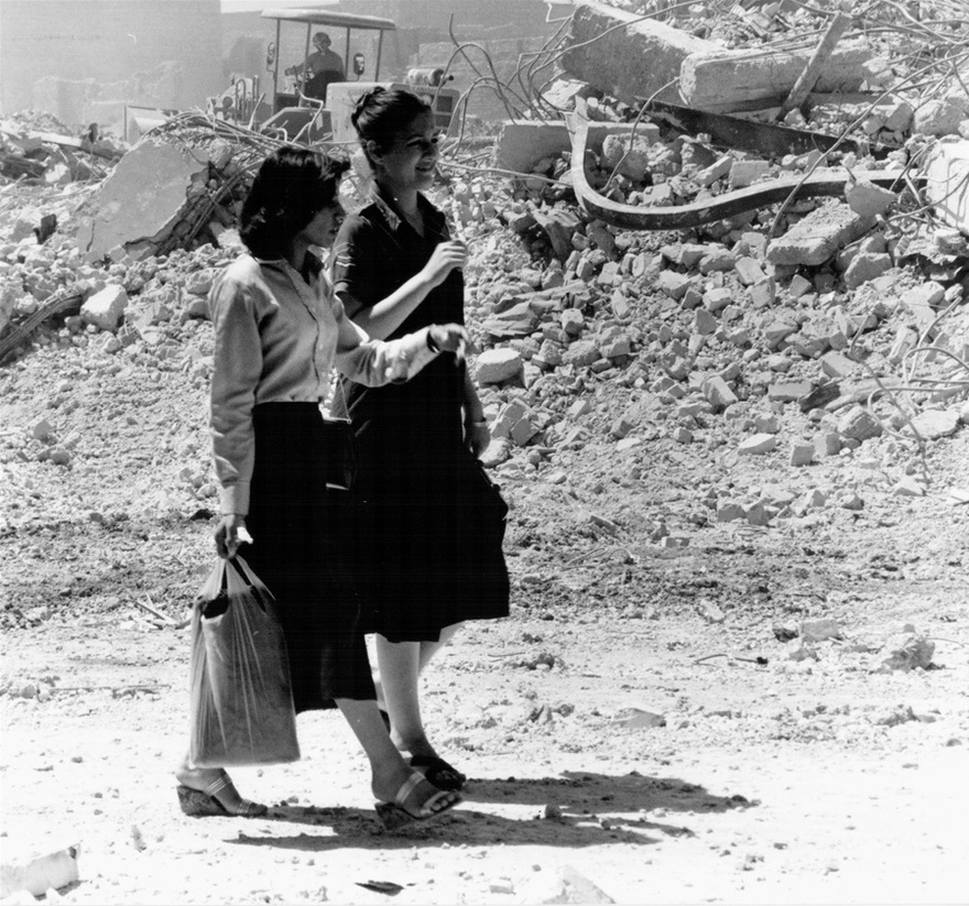 Photograph from the Chadirji collection showing women passing by rubble of the demolished area soon to become the Haifa Street development.