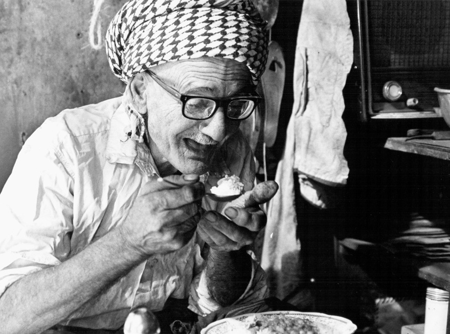 Photograph from the Chadirji collection showing traditional silversmith taking a lunch break, Baghdad.