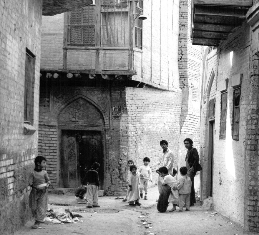 Photograph from the Chadirji collection showing children playing at a derelict alley of an old Baghdadi neighborhood.